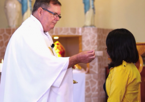 Father Paul Madden offers communion to a congregant in Puerto Huarmey, Peru. (Jimmy Chalk, GlobalPost)