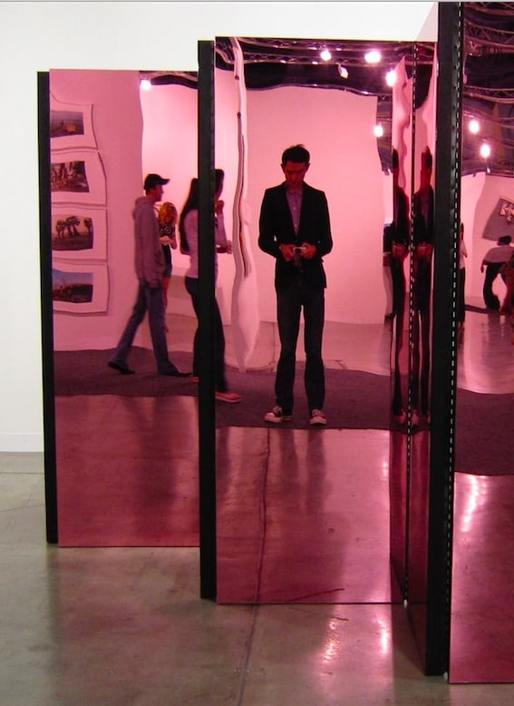 Check art, checking messages at a gallery during Art Basel in Miami in Towleroad and ManAboutWorld gay travel magazine